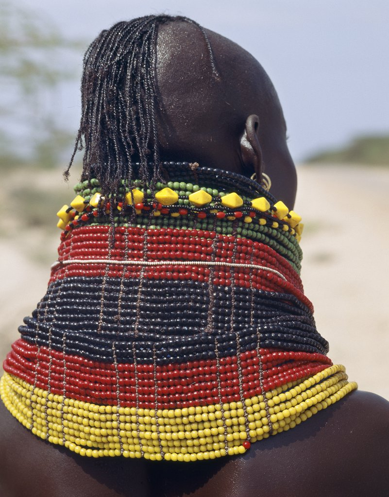 A Turkana girl's necklaces are well-oiled with animal fat and glisten in the sun.  Occasionally, a girl will put on so many necklaces that her vertebrae stretch and her neck muscles gradually weaken. The partially shaven head is typical of Turkana women and girls. : Stock Photo