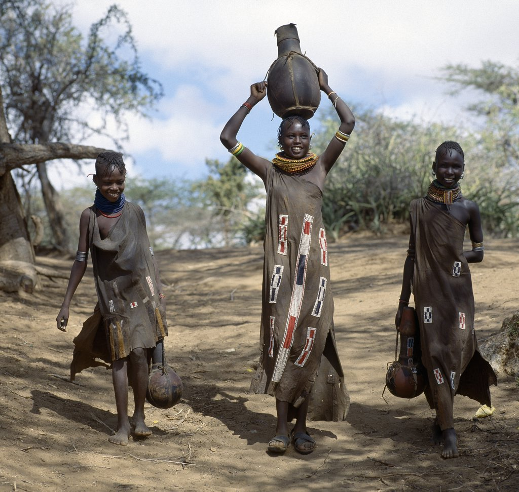 Stock Photo: 4272-16317 Turkana girls return home from a Waterhole with water containers made of wood. Their cloaks are goatskin embellished with glass beads.