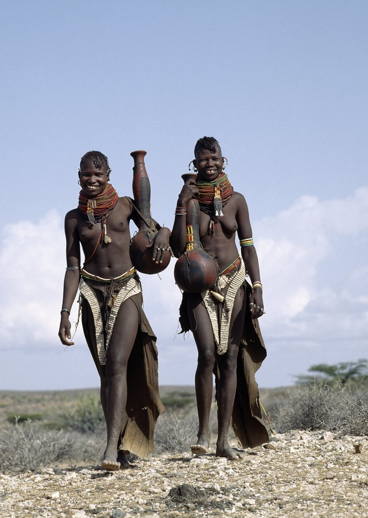 Two Turkana girls set off to fetch water from a nearby Waterhole. Their water containers are made of wood by the women of the tribe.  Their 'V' shaped aprons are made of goatskin and have been edged with hundreds and hundreds of round discs fashioned out of ostrich eggshells. : Stock Photo