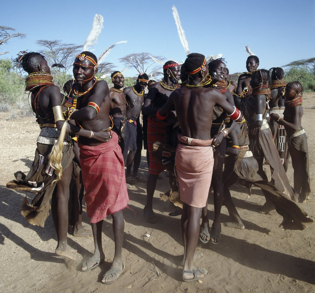 Song is an art form ingrained in Turkana culture.  In this picture, young men and girls are performing the naleyo, the only dance among a repertoire of more than twenty where couples dance together.  The songs narrate love stories about small animals such as tortoises, hares, squirrels and dikdiks. : Stock Photo