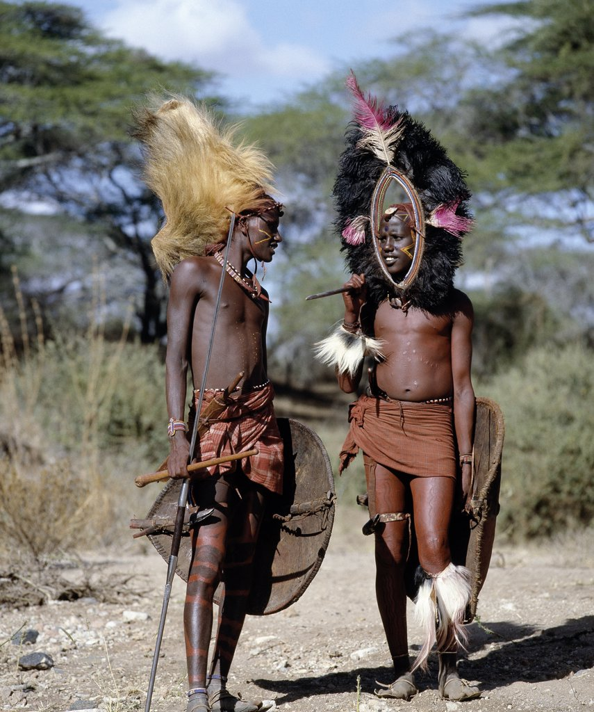 Stock Photo: 4272-16364 Two Maasai warriors in full regalia.  The headdress of the man on the left is made from the mane of a lion while the one on the right is fringed with black ostrich feathers. Their traditional weaponry includes long-bladed spears and shields are made of buffalo hide.
