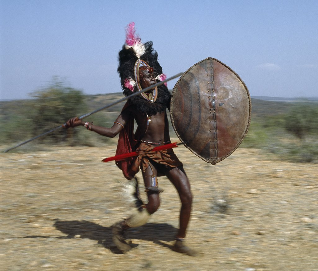 Stock Photo: 4272-16366 A Maasai warrior in full battle cry, his long-bladed spear at the ready.