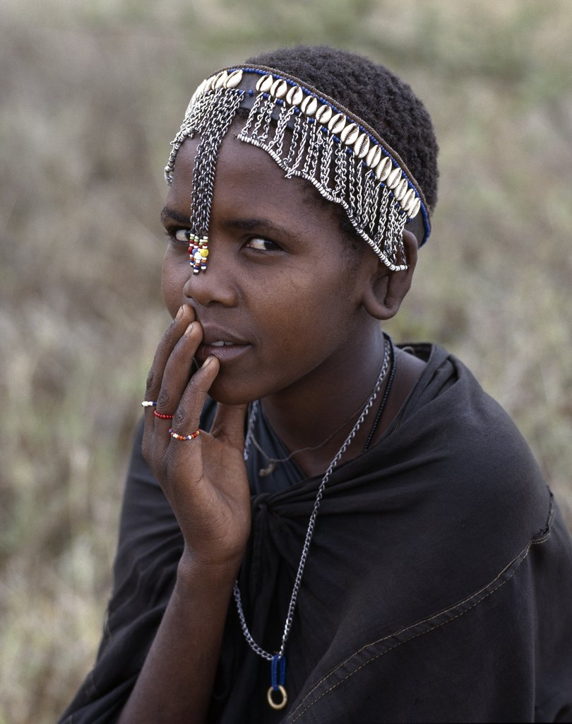 Stock Photo: 4272-16396 A young Maasai girl wears a headband decorated with chains and cowrie shells that signifies her recent circumcision. Clitodectomy was commonly practiced by the Maasai but it is now gradually dying out.