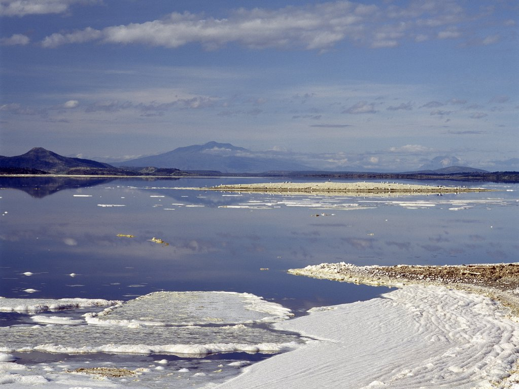 Stock Photo: 4272-16433 Lake Magadi, an alkaline lake, with Shompole - an extinct volcano - rising in the middle distance.  Ol doinyo Lengai, the only active volcano in East Africa is just visible in the far distance on the right of the picture.  Trona (Sodium sequicarbonate) has been mined at Magadi for nearly 100 years.
