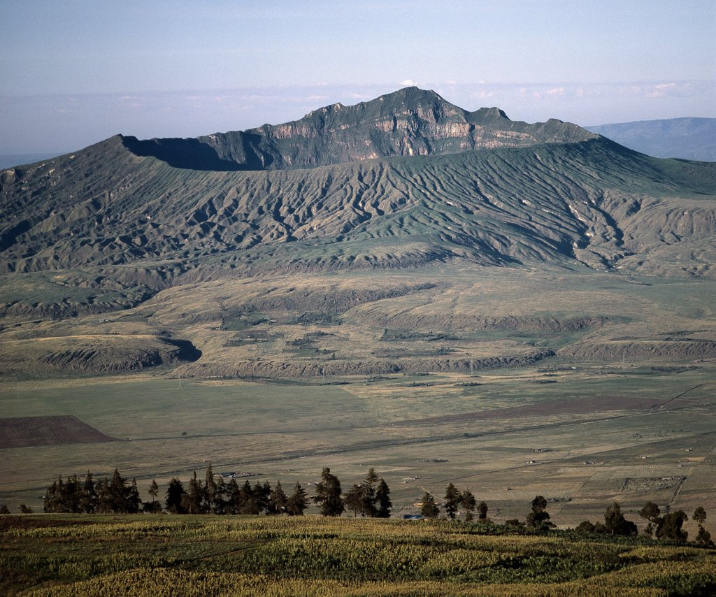 Mount Longonot, 9,110 feet high, lies on the floor of the Great Rift Valley, thirty five miles northwest of Nairobi. It is called after the apt Maasai name for it, Ol doinyo Loonongot, the mountain of many valleys and gullies. Of volcanic origin, the last eruption of a parasitic cone happened only 5,000 years ago. : Stock Photo