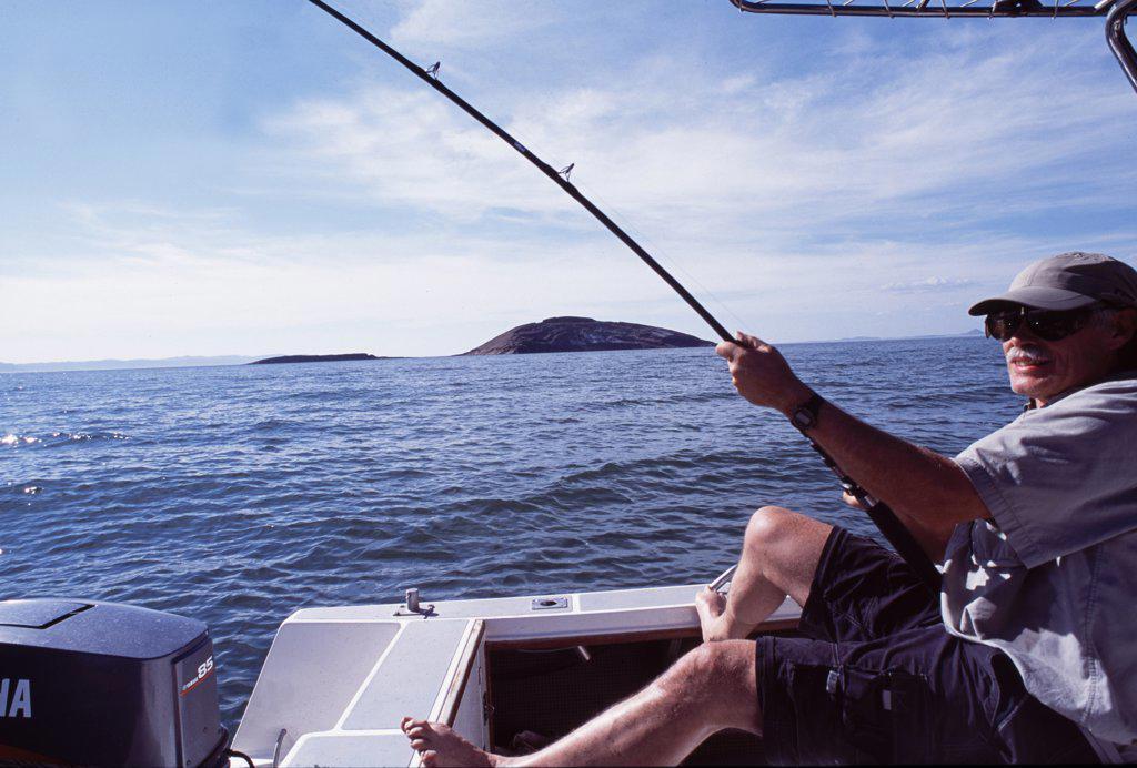 Stock Photo: 4272-16828 A fisherman braces himself to fight a Nile perch while boat fishing on Lake Turkana.