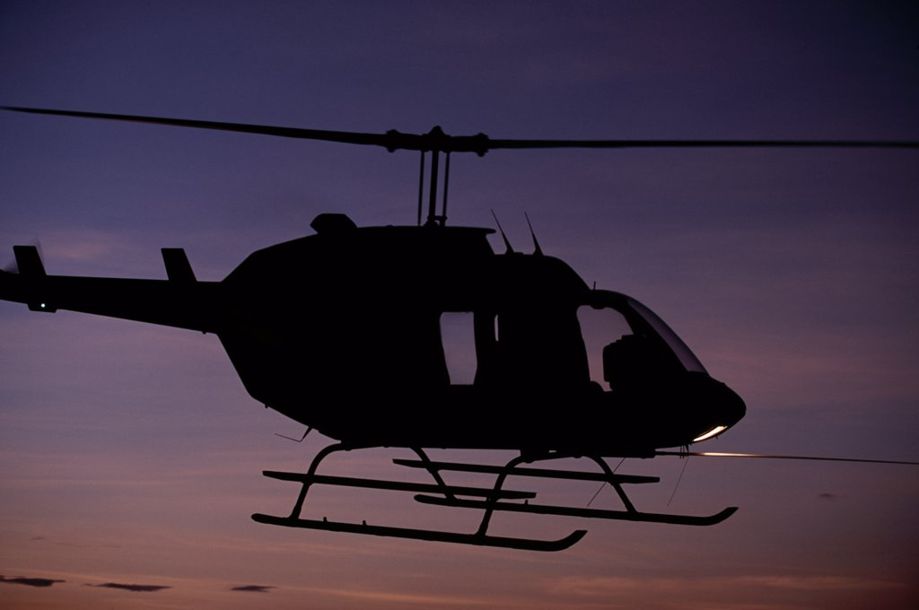 A Bell Long Ranger helicopter hovering at sunset : Stock Photo