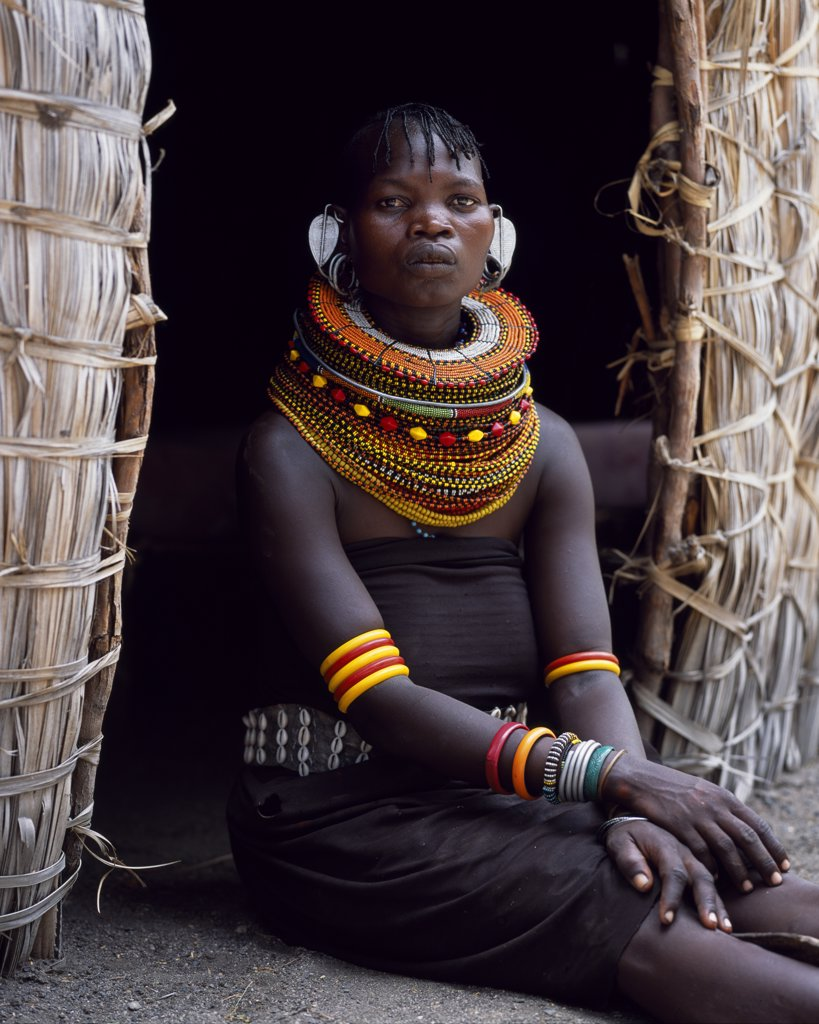 Stock Photo: 4272-16872 A Turkana woman, typically wearing many layers of bead necklaces and a series of hooped earrings with an pair of leaf-shaped earrrings at the front, sits in the entrance to her hut.
