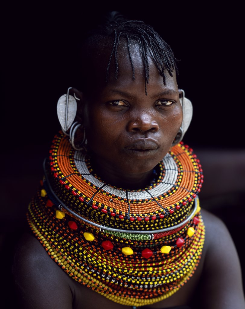 Stock Photo: 4272-16876 A Turkana woman sitting in the doorway of her hut.  Her heavy mporro braided necklace identifies her as a married woman.  Typical of her tribe, she wears many layers of bead necklaces and a beaded headband.
