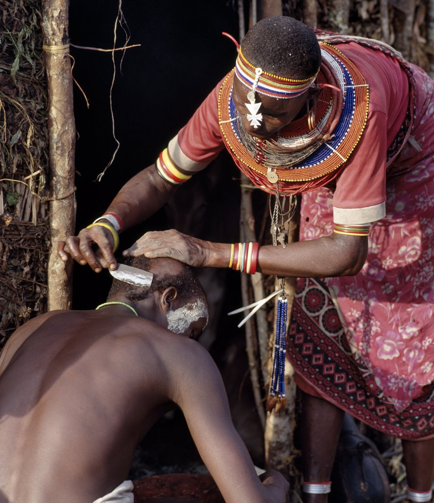 A Samburu mother shaves her sons head outside her home the day before he is circumcised. Round her neck hangs his nchipi - the distinctive decoration of every boy who participates in the circumcision ritual. : Stock Photo