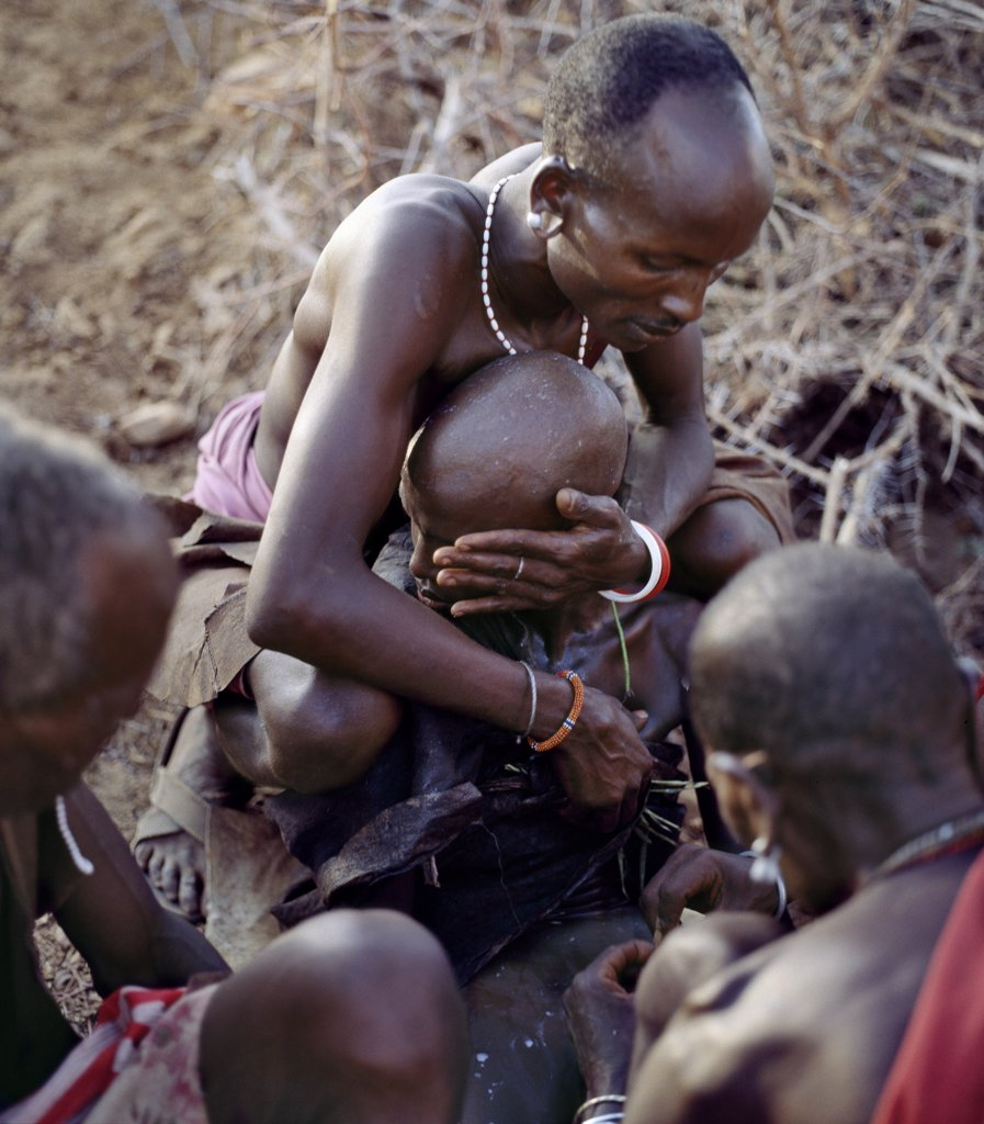Stock Photo: 4272-16964 A Samburu youth is circumcised outside his mothers house as his two sponsors attend him, one holding his shoulders while turning his face away from the circumciser, the other holding his right leg.Boys are not allowed to show any sign of fear or pain.