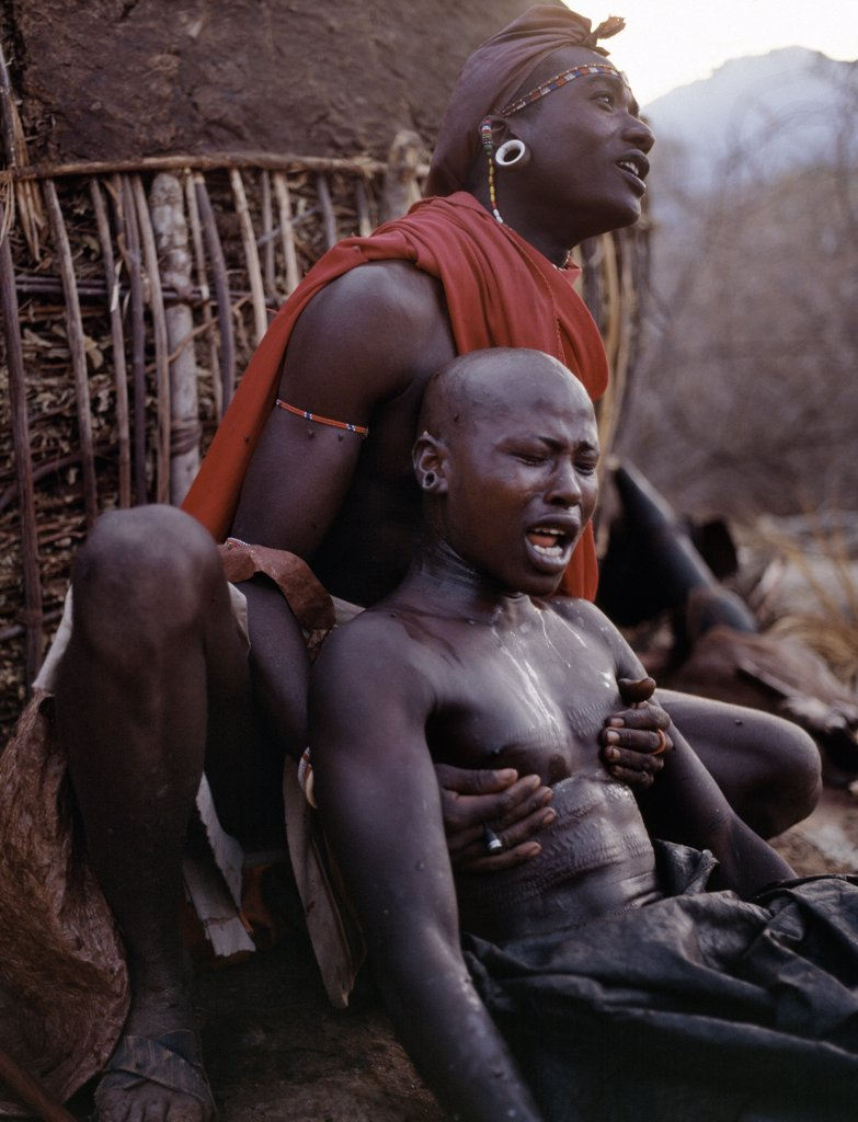 Stock Photo: 4272-16966 Early in the morning, a Samburu youth sings the lebarta, the Samburu circumcision song, just after he has been circumcised outside his mothers house. One of his sponsors attends him by holding his back. Boys are not allowed to show any sign of fear or pain.