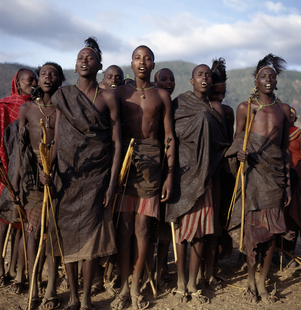 Stock Photo: 4272-16977 Samburu initiates sing during the month after their circumcision.  As their wounds heal, their dances become more energetic.  Before long, they imitate the dances of the warriors which, hitherto, they have been forbidden to perform.