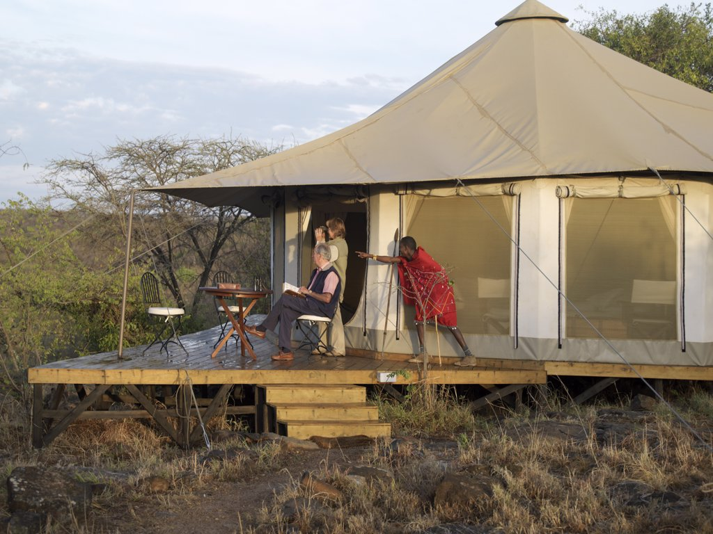 A Maasai guide points out a wild animal to visitors on the verandah of their comfortable tent at Ol Seki Tented Camp in Masai Mara Game Reserve. : Stock Photo