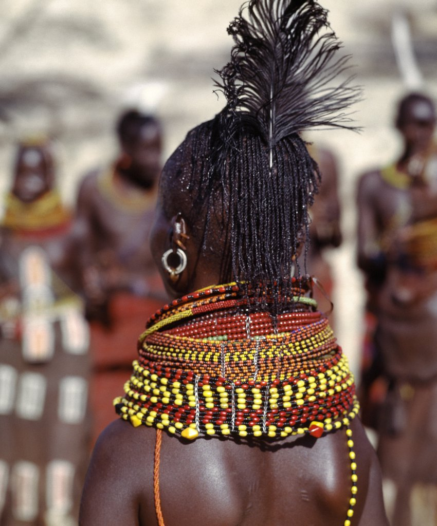 A Turkana woman with braided hair wearing heavy beaded necklaces and a black ostrich feather in the typical attire of Turkana married women. : Stock Photo