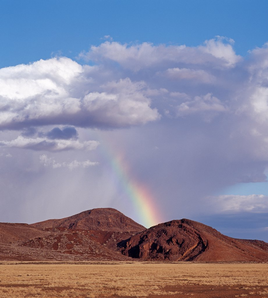 Africa, Kenya, Sirima, Turkana District. A rare shower of rain with a rainbow in the barren, lava-strewn country on southeast side of Lake Turkana. : Stock Photo