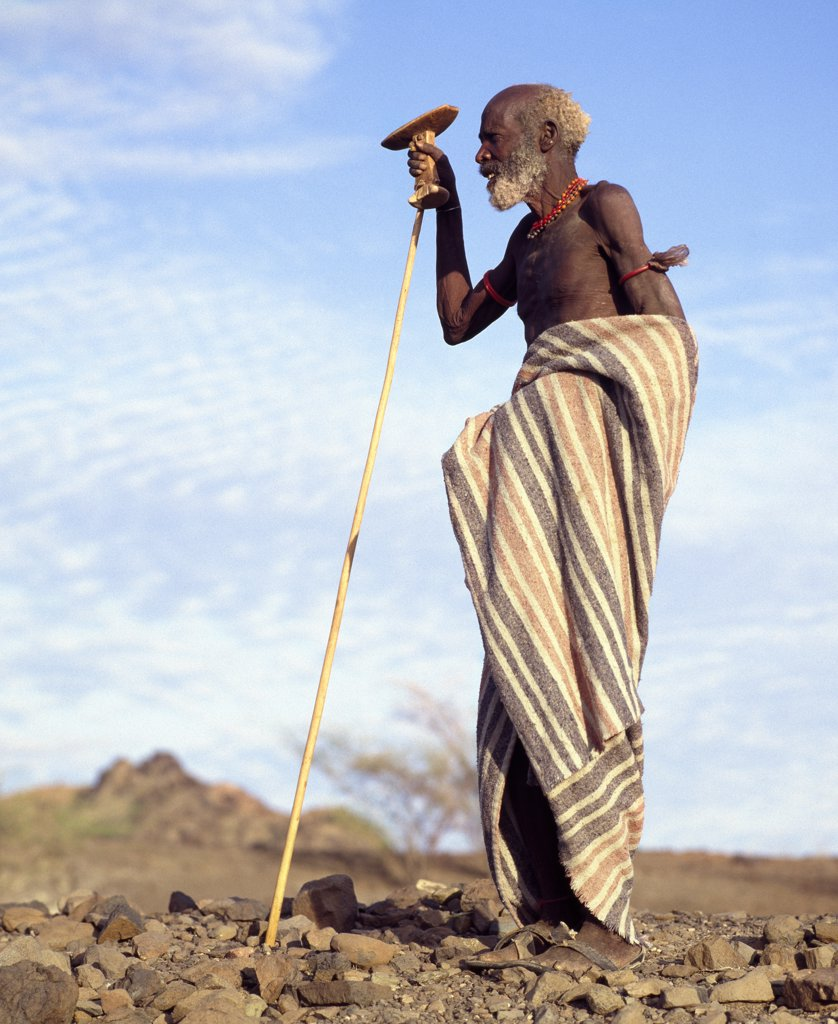 Kenya, Turkana District. An old Turkana man holding his carved wooden stool cum headrest in his right hand. : Stock Photo