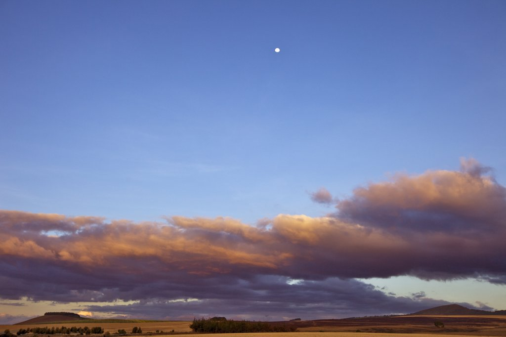 Kenya,Timau. Last light over rolling farmland at Timau with a full moon high in the sky. : Stock Photo
