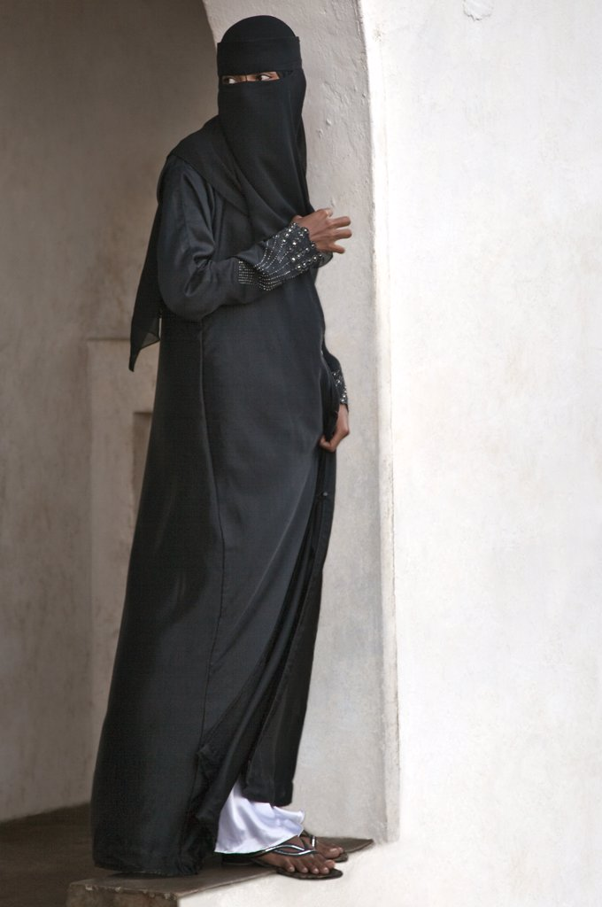 Stock Photo: 4272-18299 Kenya. A Lamu woman in fashionable Muslim dress watches the procession to mark Maulidi, from an elevated archway.