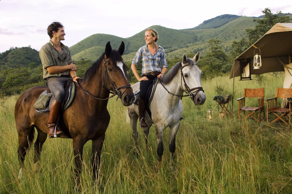 Kenya, Chyulu Hills, Ol Donyo Wuas.  Couple on a horse riding safari with Ride Africa in the Chyulu Hills (MR) : Stock Photo