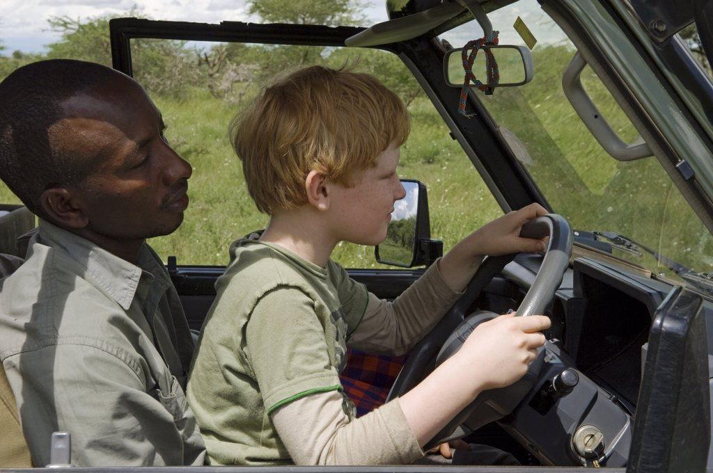 Stock Photo: 4272-18625 Kenya, Chyulu Hills, Ol Donyo Wuas. Safari guide, Moses Njoroge, lets a young guest drive the Landcruiser. (MR)
