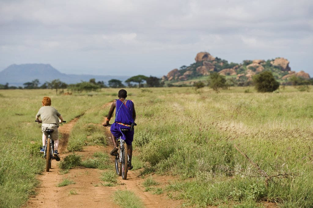 Kenya, Chyulu Hills, Ol Donyo Wuas.  A Maasai guide takes a child on a mountain biking safari. (MR) : Stock Photo