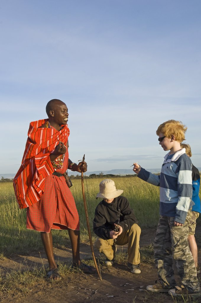 Stock Photo: 4272-18821 Kenya, Masai Mara.  Safari guide, Salaash Ole Morompi, shows porcupine quills to young boys on a family safari. (MR)