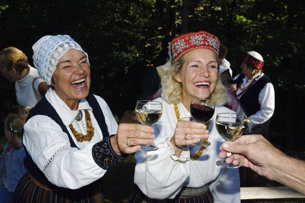 Stock Photo: 4272-19339 Woman in Traditional Dress enjoying Food and Wine at the Latvian Ethnographic Open-Air Museum