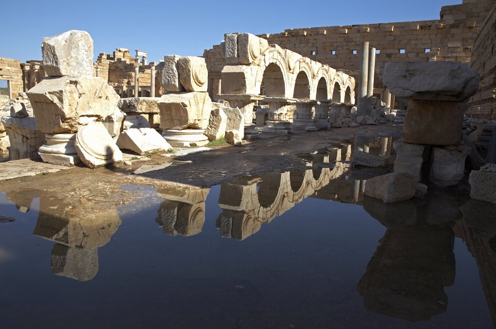 Stock Photo: 4272-19569 The remains of the facades originally built between the arches above the colonnaded porticoes of the Severan Forum, Leptis Magna, reflected in puddles left by recent rain.
