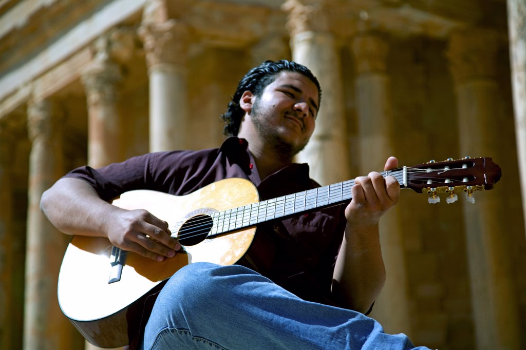 Sabratha, Libya; A young guitarist playing in front of the Theatre remains at Sabrata : Stock Photo