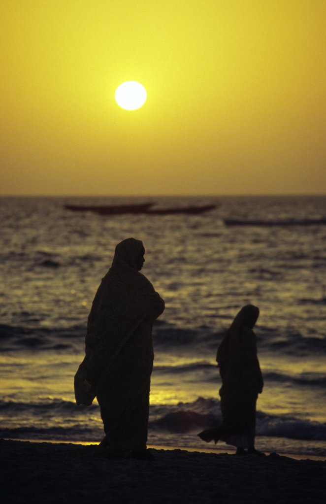 Mauritanian women shrouded in melafas are silhouetted against the afternoon sun at the Plage des Pecheurs (Fishermen's Beach) near Nouakchott.,,, : Stock Photo