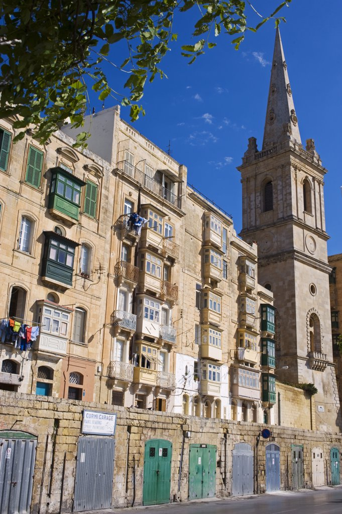 Stock Photo: 4272-21134 Malta, Valletta. A church spire rises up above closely packed apartments and garages built into the old walls of the city.