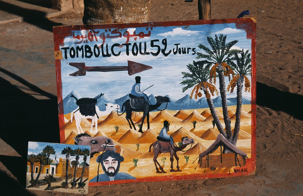 Stock Photo: 4272-21437 Painted sign pointing to Tomboutou, Timbuktu and 52 days by camel in the town of Mohammed, Draa Valley, Ouazazate Province, Southern Morocco.