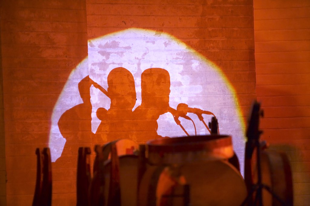 Morocco, Fes. Shadows of musicians and drums are thrown against the ancient walls of the Bab Makina during the Fes Festival of World Sacred Music. : Stock Photo
