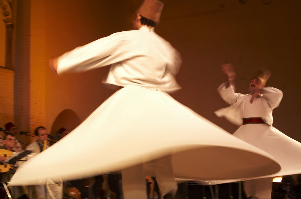 Stock Photo: 4272-21691 Morocco, Fes.  Two whirling Dervishes perform during a concert at the Fes Festival of World Sacred Music.  Members of the Al Kindi Ensemble perform the music.