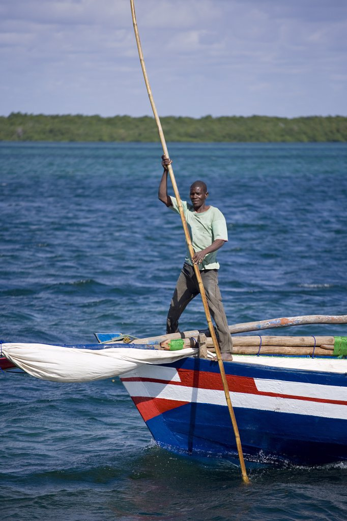Stock Photo: 4272-21905 A boatman guides a dhow into the harbour of Ibo Island, part of the Quirimbas Archipelago, Mozambique
