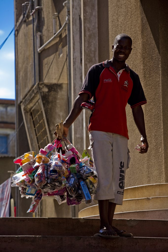 Mozambique, Maputo. A street vendor carries his products around the Polana district of Maputo - including toys, sweets and hair styling products. Maputo is the capital of Mozambique. It is a bustling, attractive port city with a population of at least 1.5 million.  Maputo is a very agreeable city which is considerably safe and more attractive when compared to other African capitals. : Stock Photo