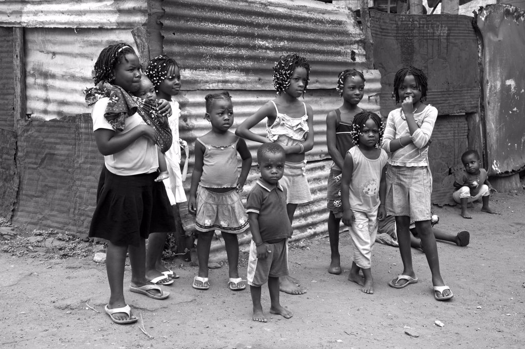 Mozambique, Maputo. A group of children crowd round the corrugated houses of their Canisa. : Stock Photo