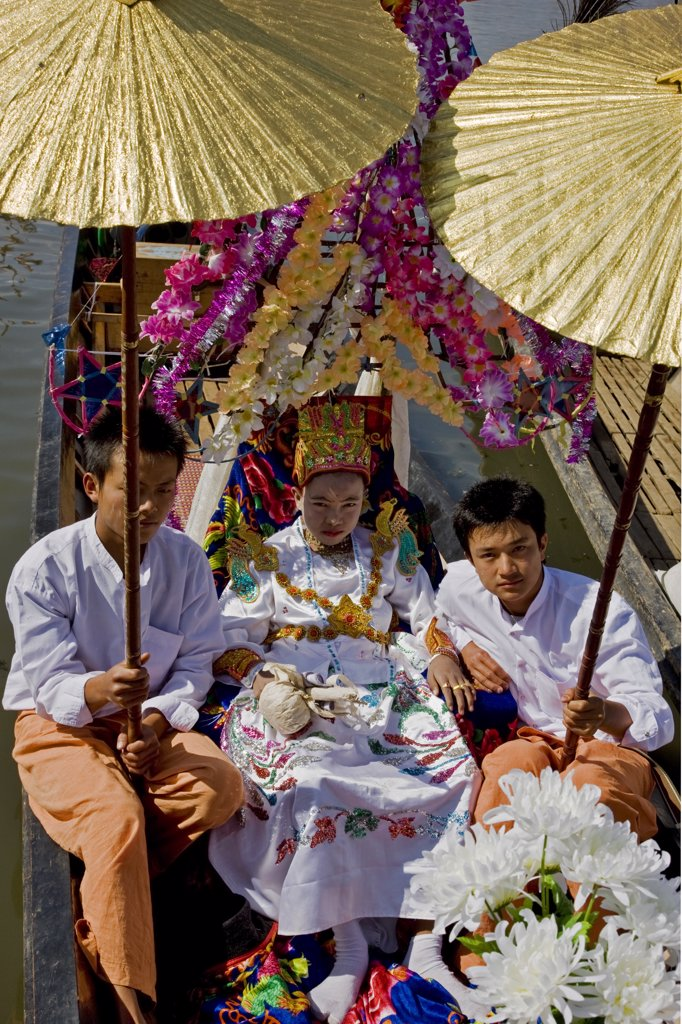Stock Photo: 4272-22532 Myanmar, Burma, Lake Inle. A young novitiate shaded with golden umbrellas during a ceremony in which the boy is inducted as a novice Buddhist monk.