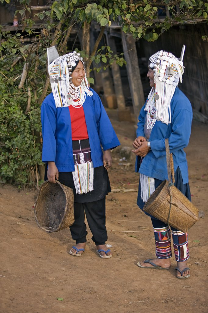 Myanmar, Burma, Namu-op. Two Akha women in all their finery pause to chat in Namu-op village. : Stock Photo