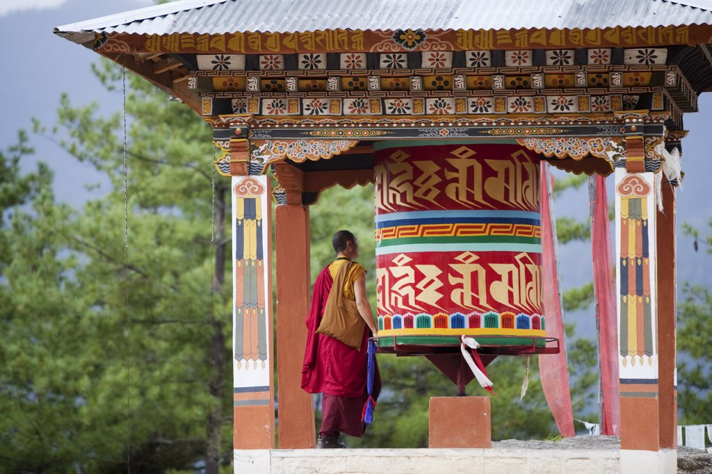 Stock Photo: 4272-2288 A monk and a prayer wheel on the path to the Paro Taktsang monastary in the Himalayan Kingdom of Bhutan