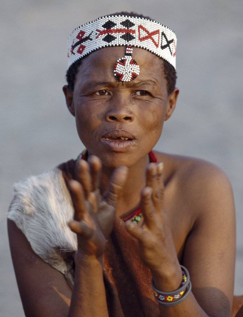 A Kung woman sings and claps her hands to the rhythm of her menfolk. The Kung are San hunter gatherers, often referred to as Bushmen. The Kung live in the harsh environment of a vast expanse of flat sand and bush scrub country straddling the Namibia Botswana border. : Stock Photo