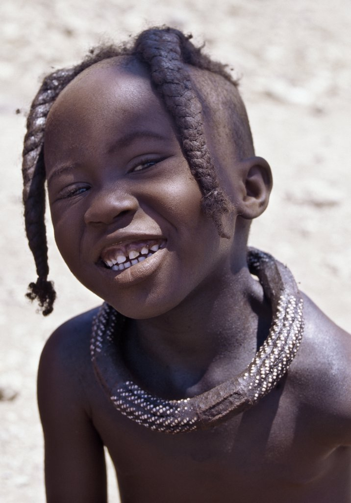 Stock Photo: 4272-23038 A Himba girl with a plaited hairstyle, which she will wear until adolescence. The Himba are Herero-speaking Bantu nomads who live in the harsh, dry but starkly beautiful landscape of remote northwest Namibia
