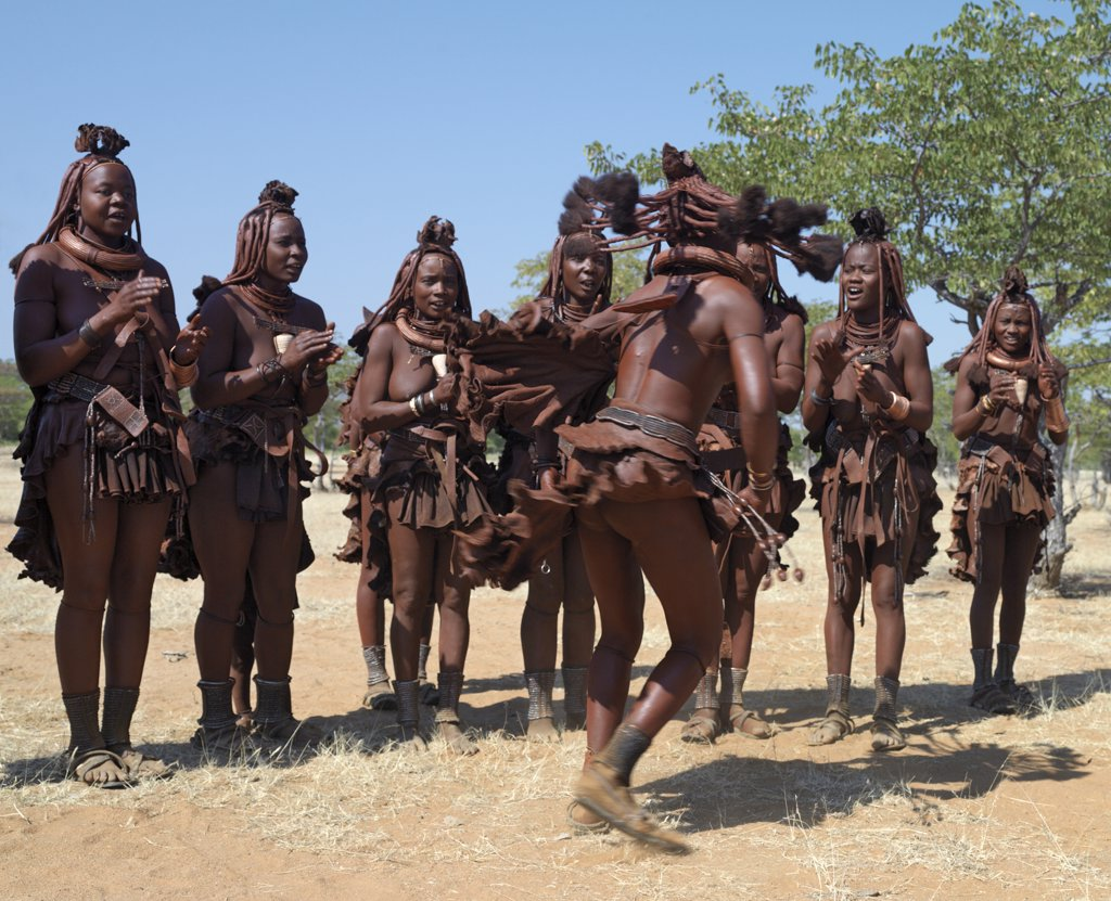 Stock Photo: 4272-23261 Himba women perform the otjiunda dance, stamping their feet, clapping and chanting while one of them gyrates in the centre of the circle. The Himba are Herero speaking Bantu nomads who live in the harsh, dry but starkly beautiful landscape of remote northwest Namibia.