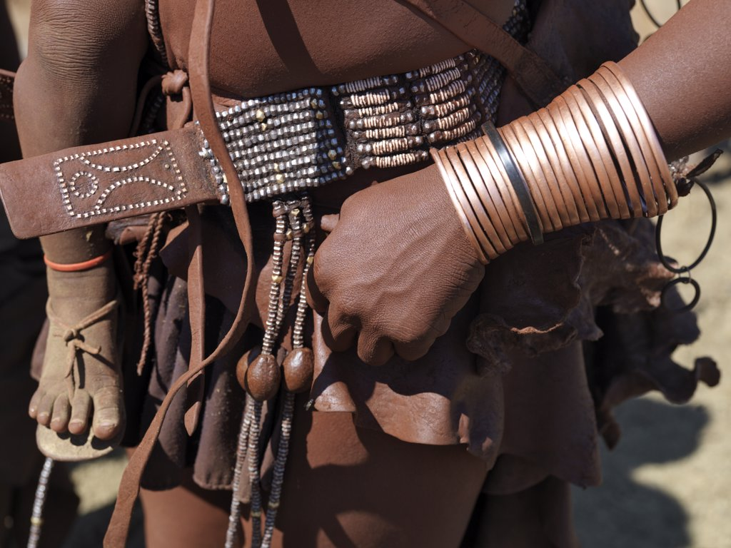 Stock Photo: 4272-23296 Himba ornaments worn by a woman. Himba women smear their bodies with a mixture of red ochre, butterfat and herbs. They still dress traditionally, wearing leather garments and a variety of ornaments made of leather with wood, ostrich shell and metal beads.  The Himba are Herero-speaking Bantu nomads who live in the harsh, dry but starkly beautiful landscape of remote northwest Namibia.