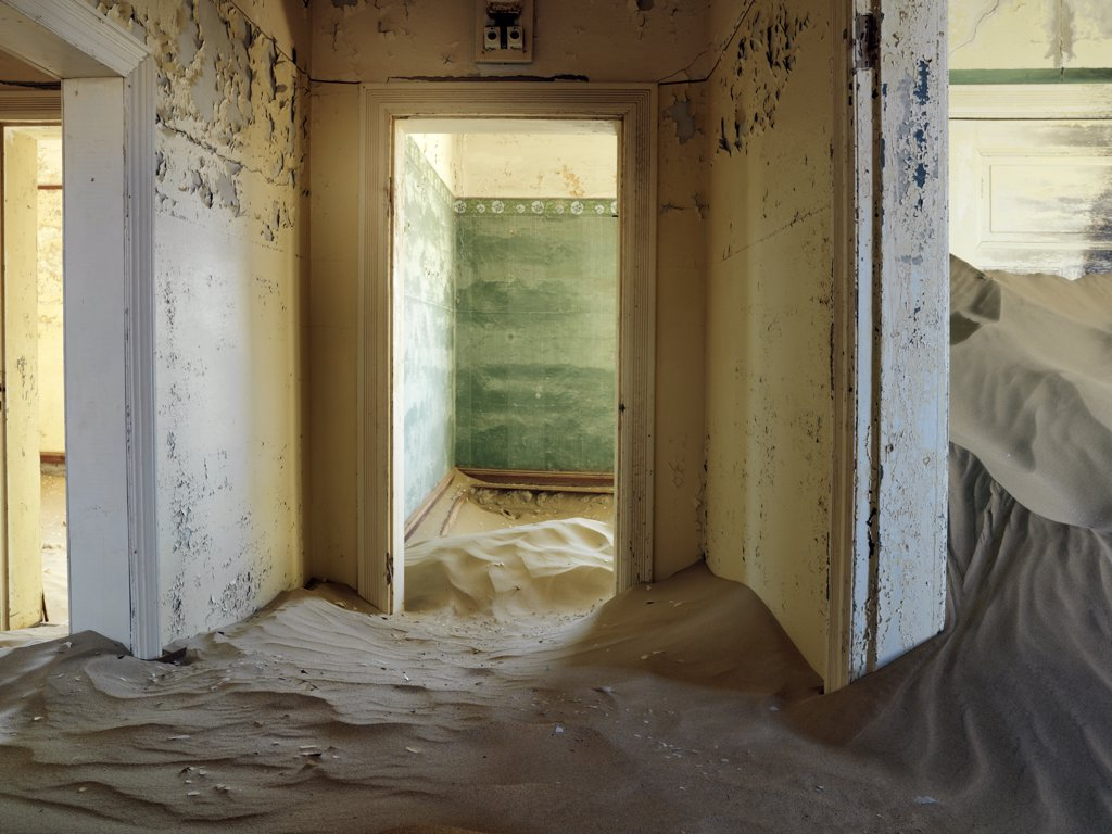 A scene in the deserted diamond-mining town of Kolmanskop, which was abandoned more than fifty years ago.  The place is now a ghost town where sand from the surrounding desert has encroached into all the old buildings of this once prosperous place. : Stock Photo