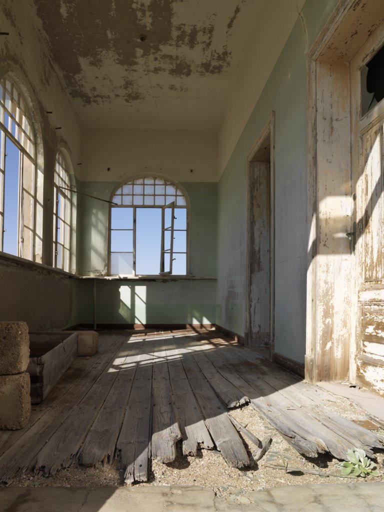 Stock Photo: 4272-23331 A scene in the deserted diamond-mining town of Kolmanskop, which was abandoned more than fifty years ago.  The place is now a ghost town where sand from the surrounding desert has encroached into all the old buildings of this once prosperous place.