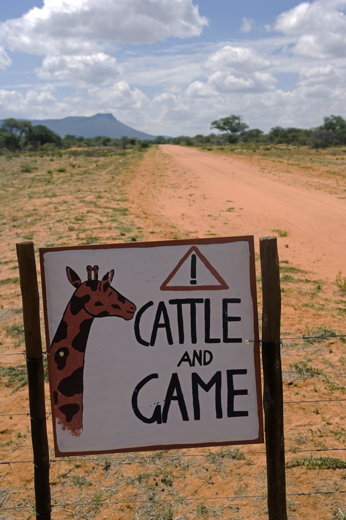 Namibia, Erongo Region. Where a dirt track bisects a bush farm, a sign on the road warns of the danger of speeding to cattle and game animals. : Stock Photo