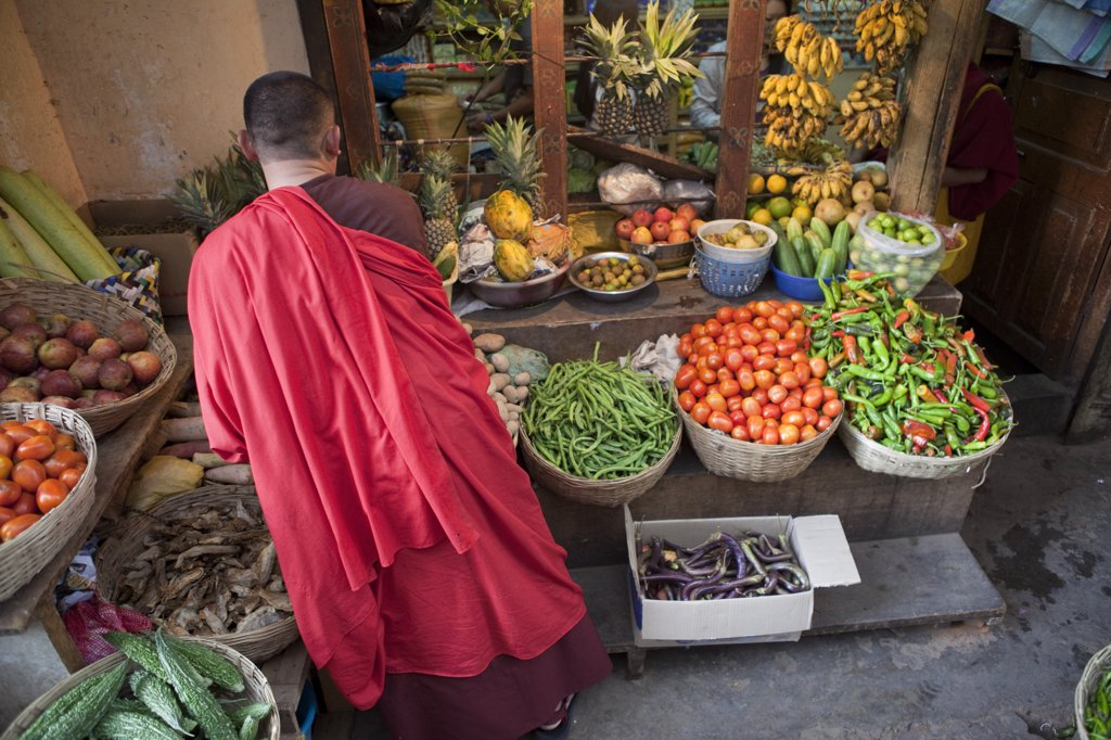 A buddist monk shopping for produce in Thimphu Bhutan : Stock Photo