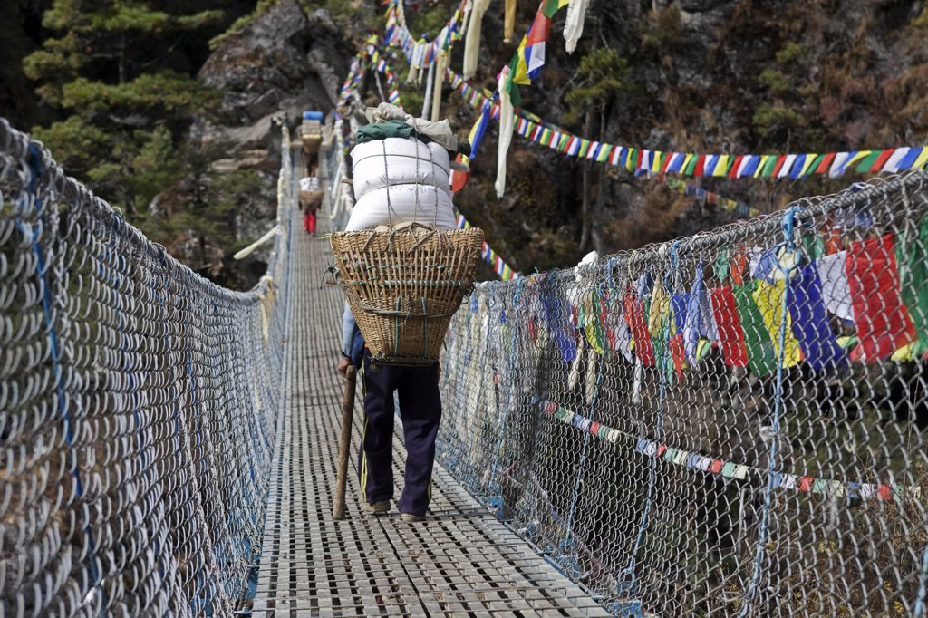 Stock Photo: 4272-24044 Nepal, Everest Region, Khumbu Valley. Heavily laden porters cross wire suspension bridge on the Everest Base Camp Trek near Namche Bazaar